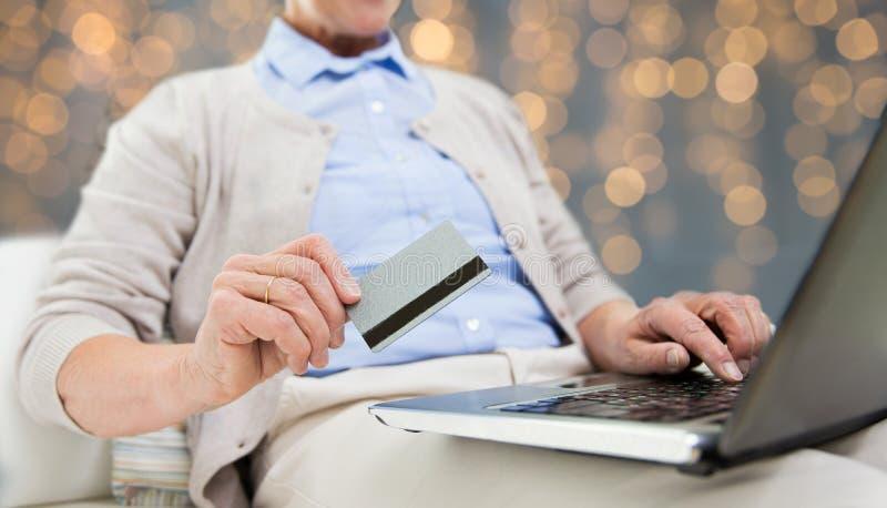 Mulher superior com portátil e cartão de crédito foto de stock