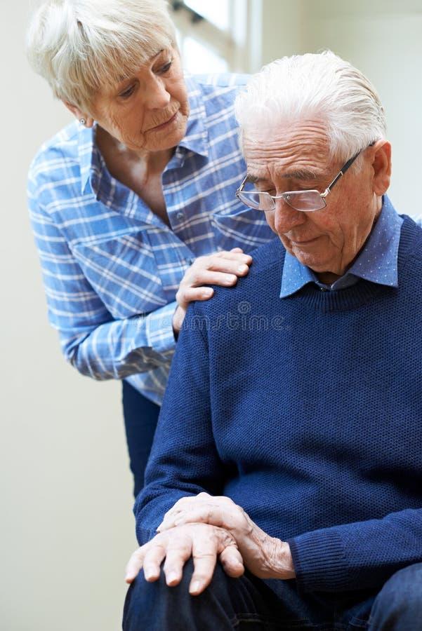 A mulher superior consola o marido que sofre com Parkinsons Diesease fotografia de stock