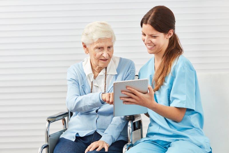 Mulher superior curiosa na cadeira de rodas com PC da tabuleta imagem de stock royalty free