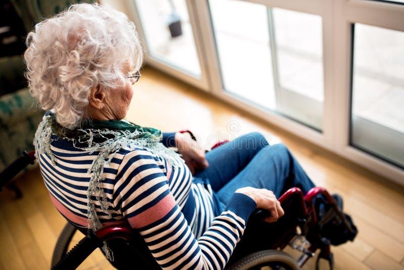 Mulher superior da solidão triste da depressão na cadeira de rodas fotografia de stock