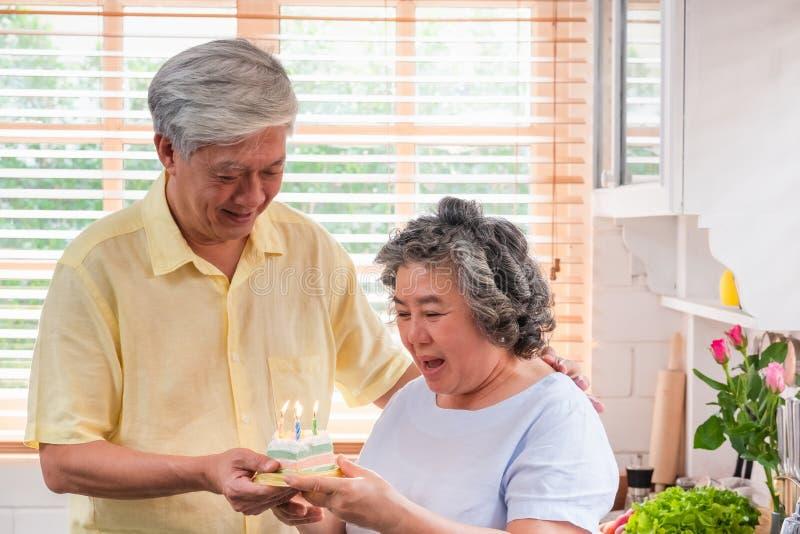 Mulher superior da surpresa asiática do homem superior com o bolo de aniversário na cozinha em casa envelhecendo em casa o concei fotografia de stock royalty free