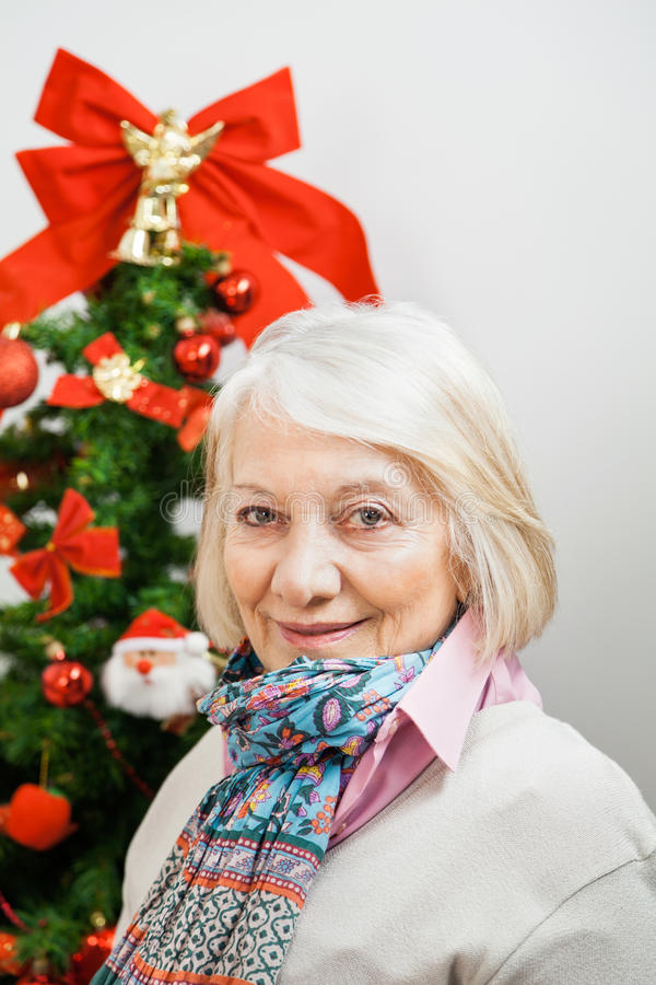 Mulher superior de sorriso contra a árvore de Natal foto de stock