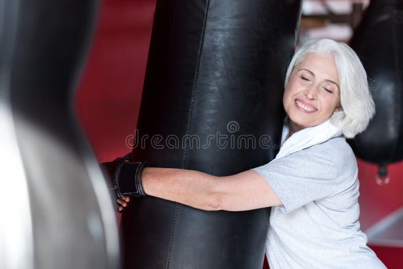 Mulher superior de sorriso emocional que abraça o saco de perfuração fotografia de stock