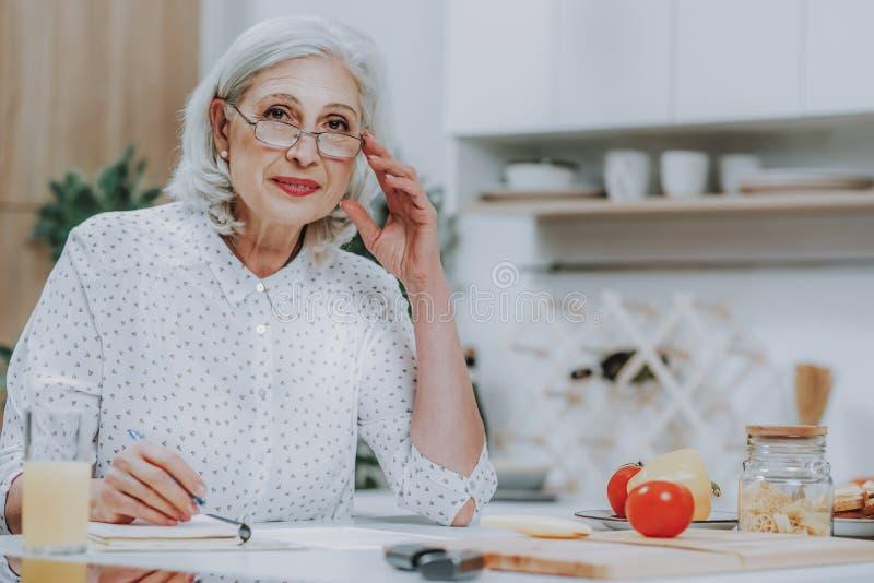 A mulher superior de sorriso está escrevendo na mesa de cozinha fotos de stock royalty free