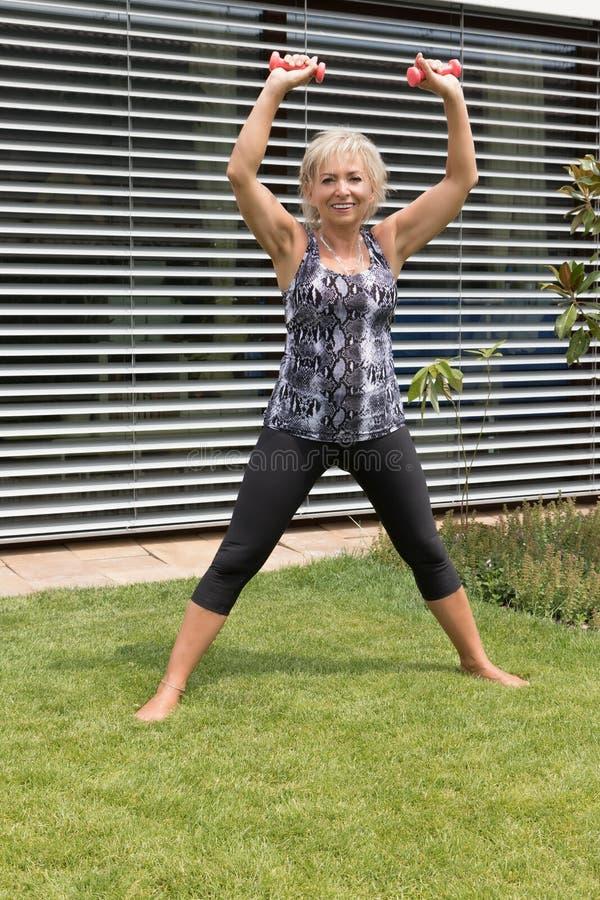 A mulher superior de sorriso está exercitando com pesos fora Vert fotos de stock