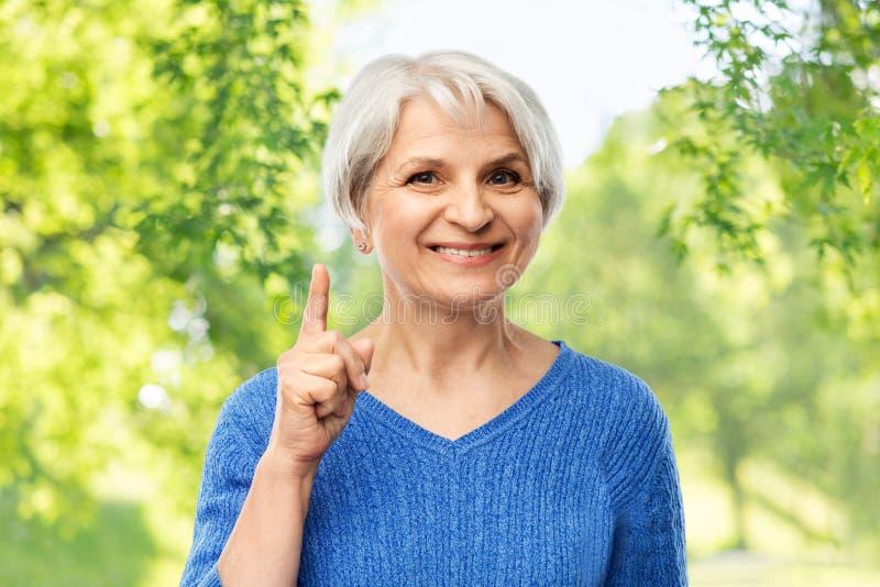 Mulher superior de sorriso que aponta o dedo acima imagens de stock