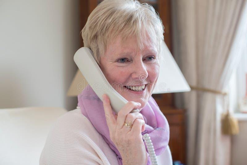 Mulher superior de sorriso que faz o telefonema em casa foto de stock
