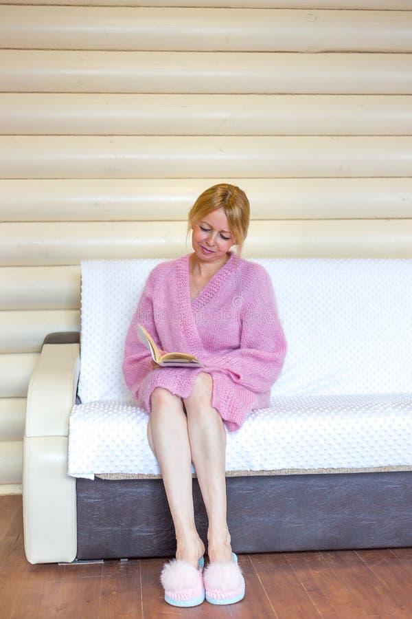 Mulher superior de sorriso que lê um livro em casa fotos de stock