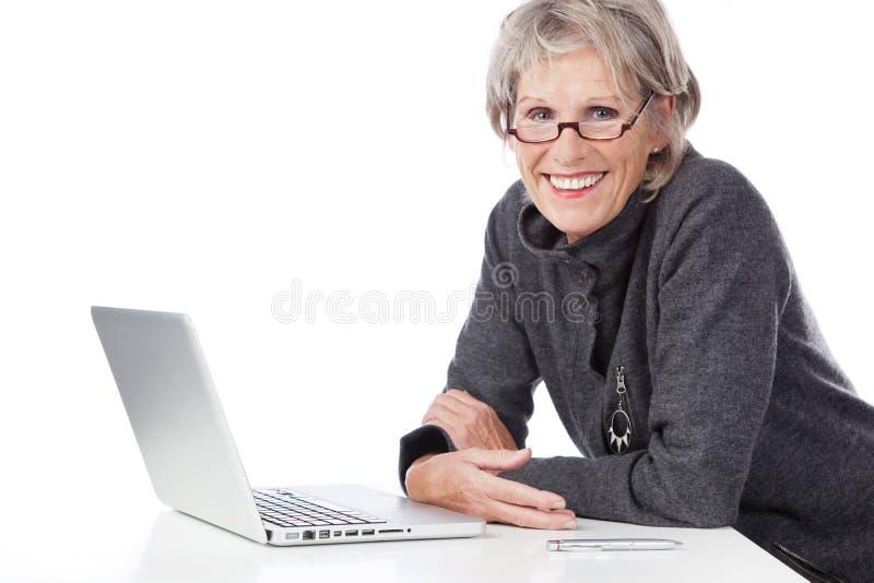 Mulher superior de sorriso que usa um computador portátil