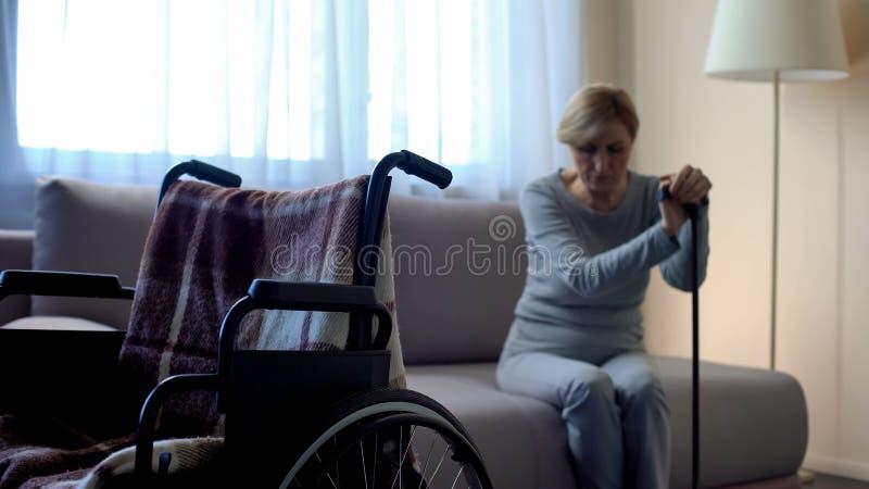 Mulher superior deficiente infeliz que olha a cadeira de rodas vazia, solidão fotos de stock royalty free