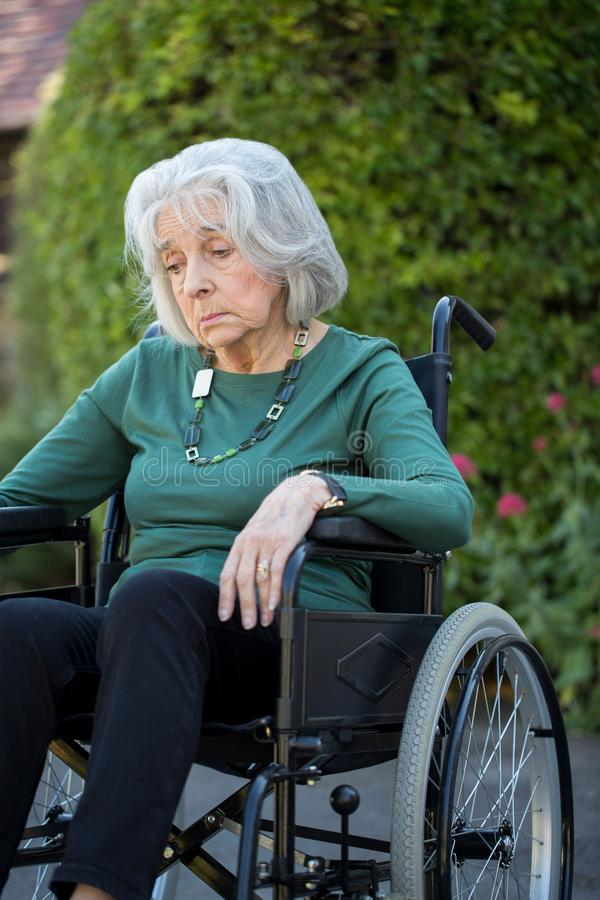 Mulher superior deprimida na cadeira de rodas que senta-se fora foto de stock royalty free