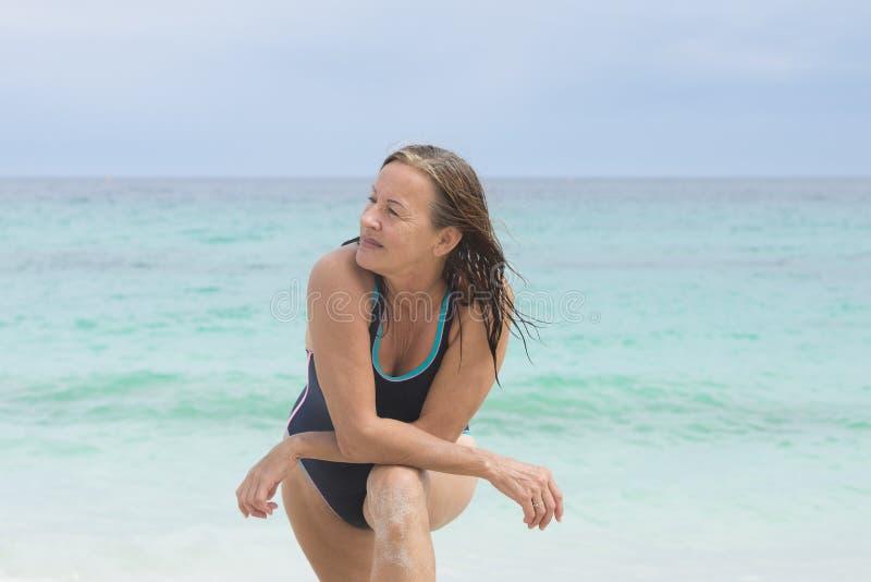 Mulher superior desportiva na praia imagem de stock royalty free