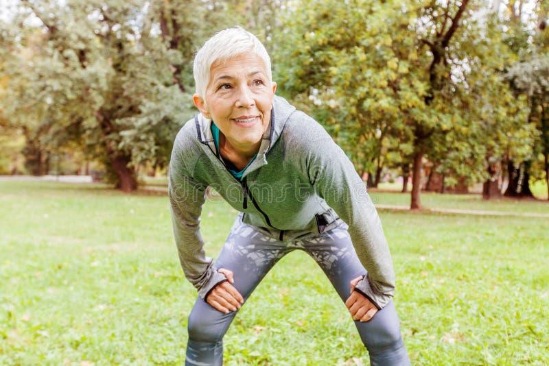 Mulher superior do ajuste pronta para correr na natureza fotografia de stock royalty free