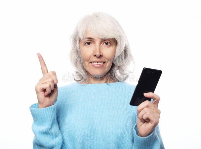 A mulher superior do smiley está guardando um smartphone novo em sua mão imagem de stock