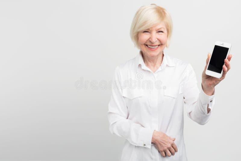 A mulher superior do smiley está guardando um smartphone novo em sua mão Aprendeu como usá-lo Passioned aproximadamente imagens de stock royalty free