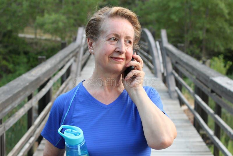 Mulher superior do turista que usa uma comunicação esperta do curso do parque da árvore do verde das férias de verão do sorriso d imagem de stock