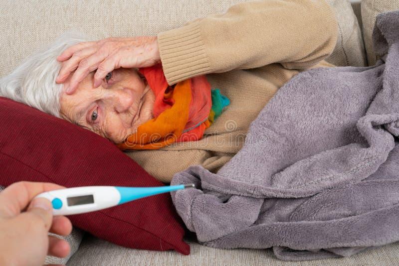 Mulher superior doente - febre fotografia de stock royalty free