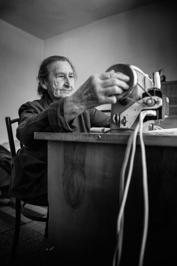 Mulher superior dos anos de idade 80 positivos bonitos que usa a máquina de costura do vintage A imagem preto e branco da costura fotos de stock