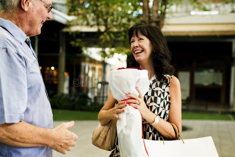 Mulher superior dos pares que guarda o ramalhete das rosas imagens de stock royalty free