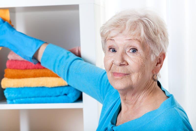Mulher superior durante tarefas de agregado familiar imagens de stock