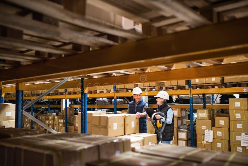 Mulher superior e gerentes ou supervisores do homem que trabalham em um armazém foto de stock