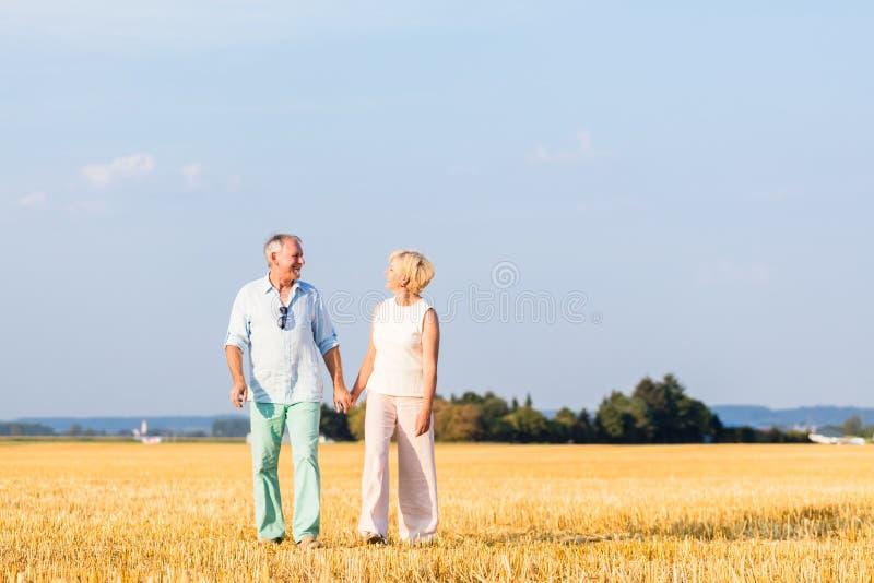 Mulher superior e homem que guardam as mãos que têm a caminhada fotos de stock