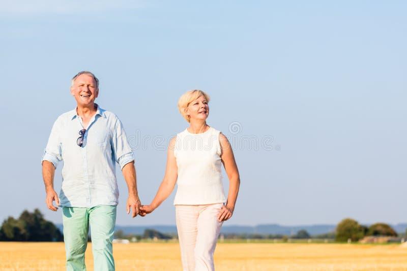Mulher superior e homem que guardam as mãos que têm a caminhada fotografia de stock royalty free