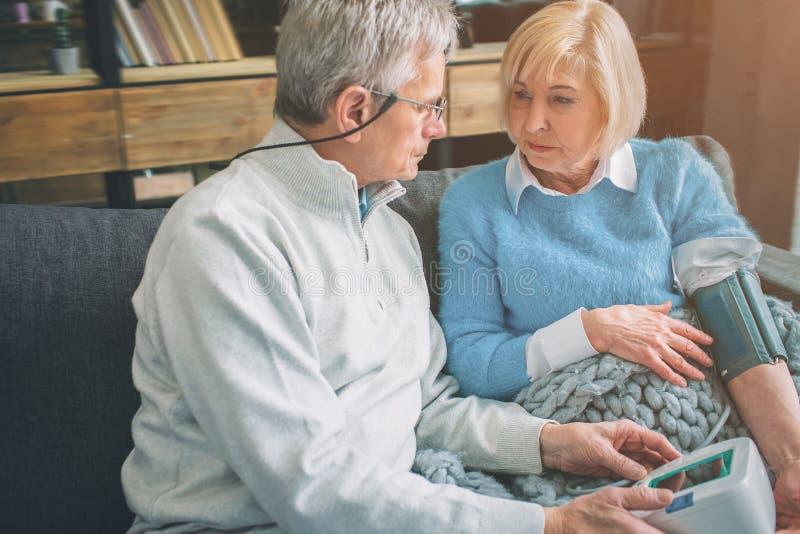 A mulher superior está medindo sua pressão sanguínea com um devi especial fotos de stock