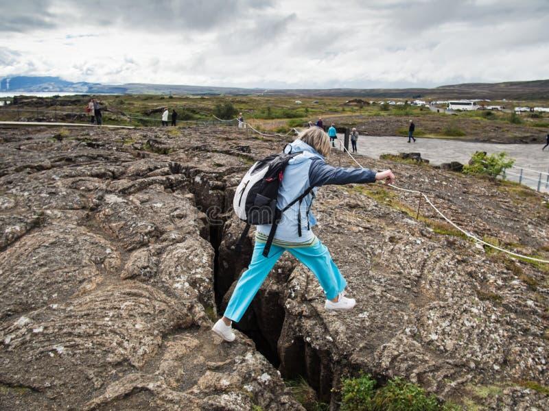 A mulher superior está saltando sobre uma diferença da terra em Thingvellir Nationa fotografia de stock royalty free