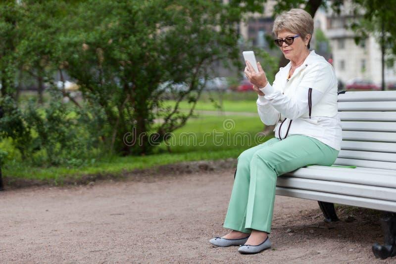Mulher superior europeia que datilografa uma mensagem no telefone celular ao sentar-se no banco no parque do verão, espaço da cóp fotos de stock