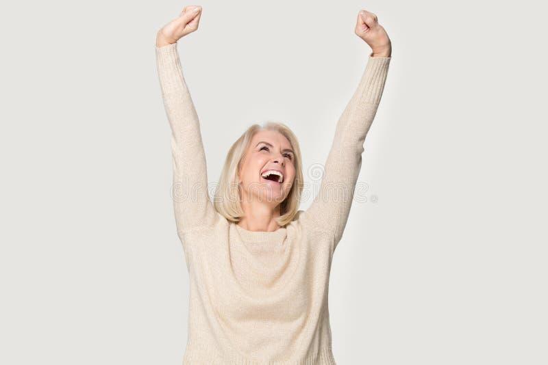 A mulher superior excitada levantou as mãos esticadas sente o tiro feliz do estúdio fotos de stock royalty free