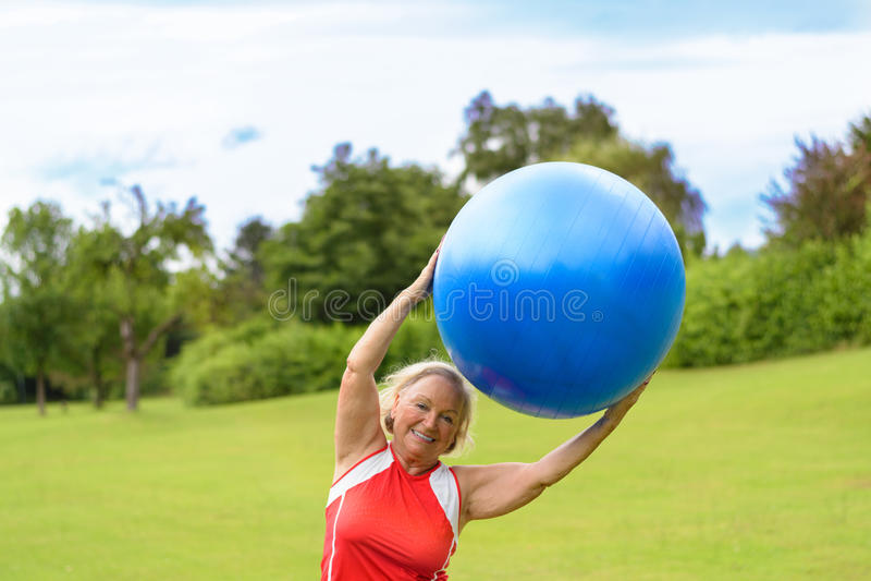 Mulher superior feliz com a bola da estabilidade aérea imagem de stock royalty free