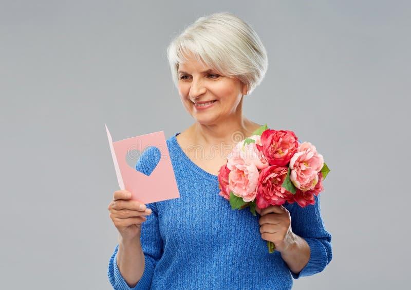 Mulher superior feliz com flores e cartão imagem de stock royalty free