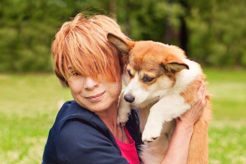 Mulher superior feliz com seu cachorrinho do cão do amigo do animal de estimação que afaga na grama verde no retrato do parque do fotografia de stock