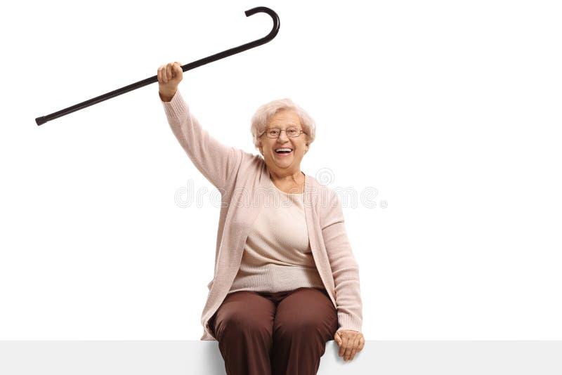 Mulher superior feliz com um bastão que senta-se em um painel fotografia de stock royalty free