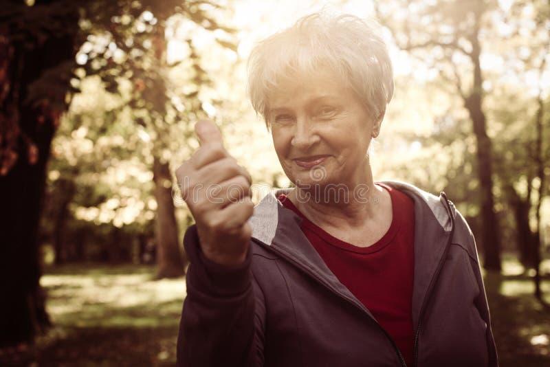 Mulher superior feliz de sorriso na roupa dos esportes que mostra ESTÁ BEM fotografia de stock royalty free