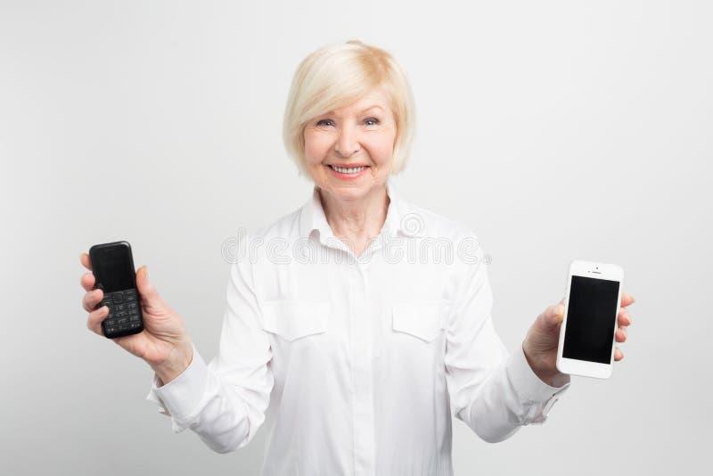 A mulher superior feliz está guardando um telefone velho com botões e um telefone novo com tela grande Usou-se para usar ambos imagens de stock royalty free