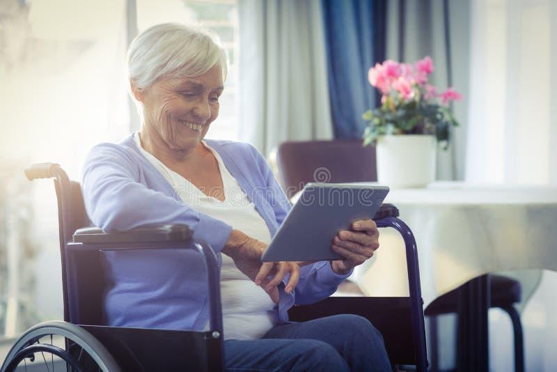 Mulher superior feliz na cadeira de rodas usando a tabuleta digital fotografia de stock