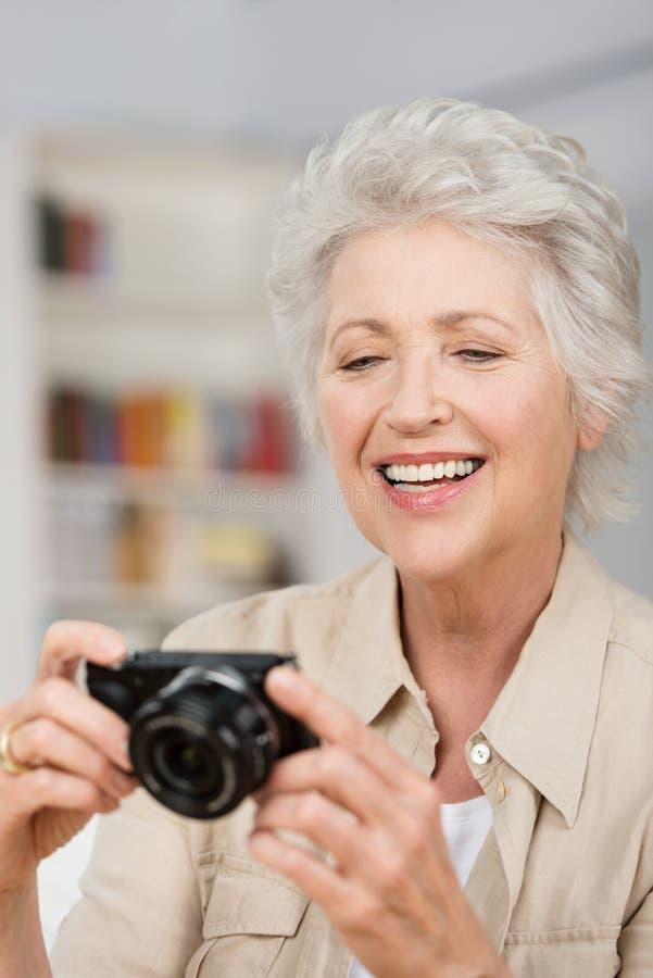 Mulher superior feliz que ajusta sua câmera compacta imagens de stock