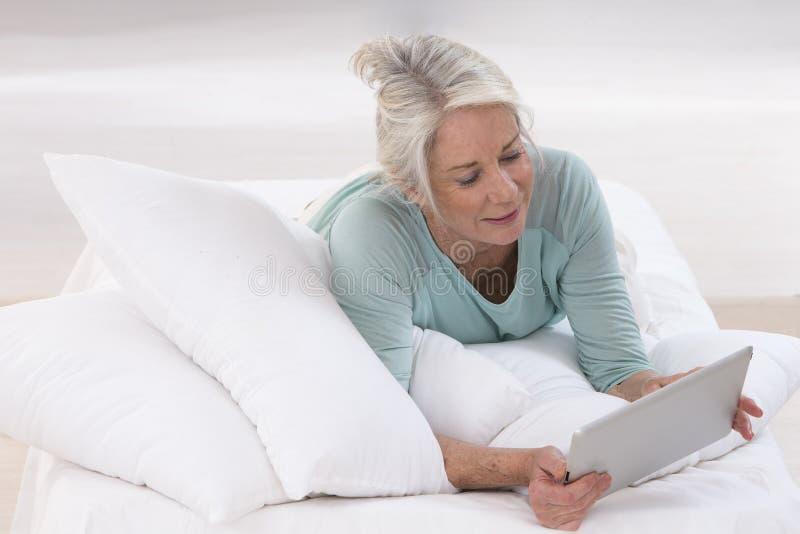 mulher superior feliz que encontra-se na cama e na utilização imagens de stock
