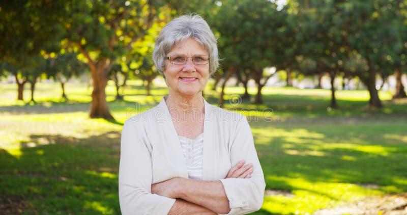 Mulher superior feliz que está no parque imagens de stock