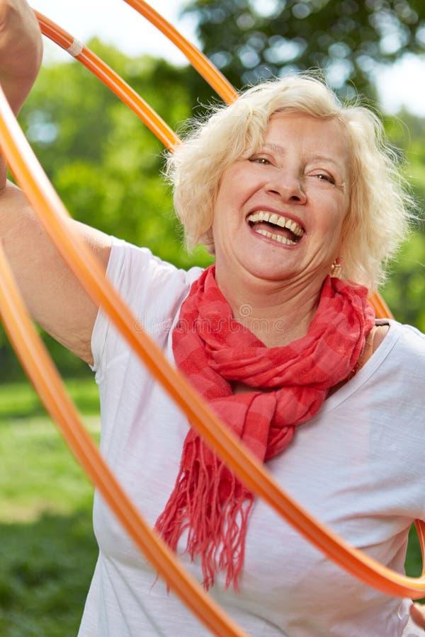 Mulher superior feliz que faz esportes com aro fotografia de stock