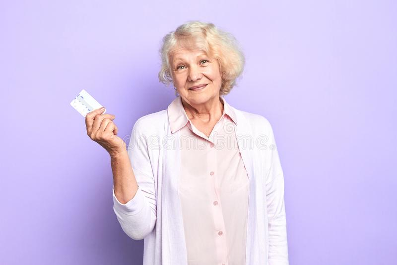 Mulher superior feliz que guarda o cartão de crédito disponível que sorri e que olha a câmera fotografia de stock