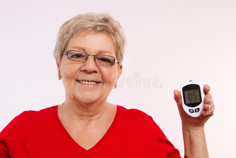 Mulher superior feliz que guarda o glucometer, medindo e verificando o nível do açúcar, conceito do diabetes na idade avançada imagens de stock