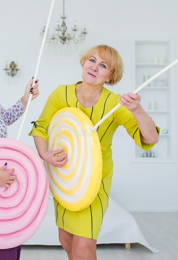 Mulher superior feliz que joga a guitarra doce Mulher de surpresa do guloso cercada por doces do brinquedo e por gelado imagens de stock