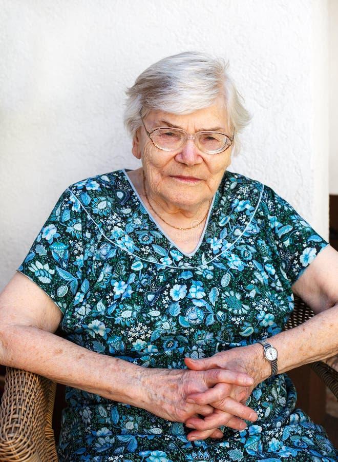 Mulher superior feliz que relaxa no jardim do verão. imagens de stock royalty free