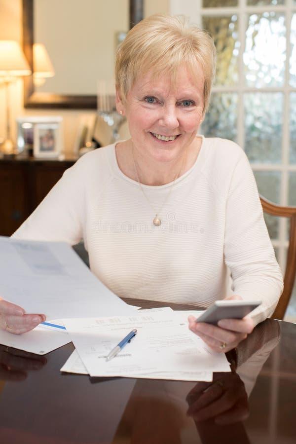 Mulher superior feliz que revê finanças domésticas em casa foto de stock