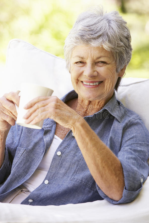 Mulher superior feliz que senta-se em Sofa With Drink fotografia de stock royalty free