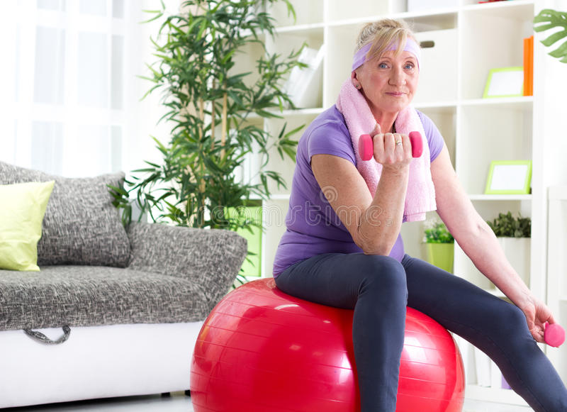 Mulher superior feliz que sentam-se na bola do gym, e exercício foto de stock