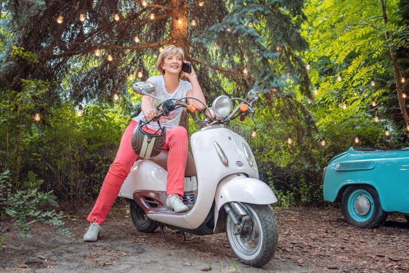 Mulher superior idosa bonita no velomotor retro ou na bicicleta motorizada que falam no telefone foto de stock